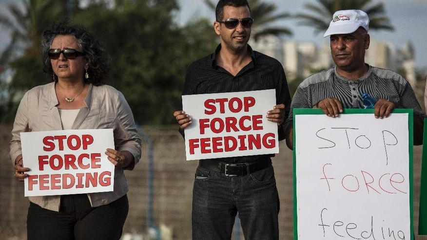In this Tuesday, August 11, 2015 file photo, Israeli Arab supporters of Mohammed Allan, a Palestinian prisoner on a hunger strike, hold signs during a rally outside Barzilai hospital, in the costal city of Ashkelon, Israel. Allan spent his college years as an activist, fighting for Palestinian rights as a member of the student wing of the Palestinian Islamic Jihad militant group. Now, verging on death and shackled to a hospital bed, the man accused by Israel of affiliation with terrorists has put a spotlight on Israel's controversial detention and force-feeding policies. (AP Photo/Tsafrir Abayov, File)