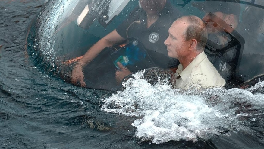 ALTERNATIVE CROP OF MOSB102 Russian President Vladimir Putin, right, sits on board a bathyscaphe as it plunges into the Black sea along the coast of Sevastopol, Crimea, Tuesday, Aug. 18, 2015. President Vladimir Putin plunged into the Black Sea to see the wreckage of a sunk ancient merchant ship which was found in the end of May. (Alexei Nikolsky/RIA-Novosti, Kremlin Pool Photo via AP)