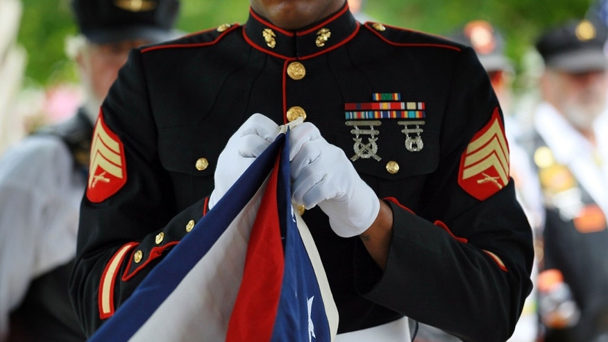 "LAKE WORTH, FL - MAY 29: A U.S. Marine folds the American flag that was drapped over the casket of U.S. Marine Lance Corporal Patrick Xavier Jr. during a burial ceremony at the South Florida National Cemetery on May 29, 2010 in Lake Worth, Florida. Patrick Xavier Jr. was killed May 18th during a ""hostile incident"" in the Helmand province region of Afghanistan..  (Photo by Joe Raedle/Getty Images)"