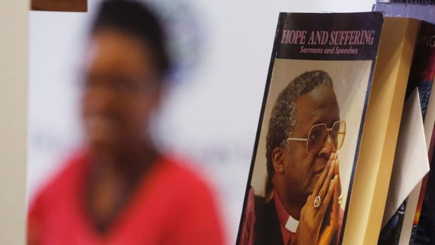 Reverend Mpho Tutu, the daughter of retired South African Archbishop Desmond Tutu, speaks to the media during a press briefing  as a book, right, written by Desmond Tutu, is displayed on a bookshelf  in Cape Town, South Africa, Tuesday, Aug. 18, 2015. Tutu is back in a hospital for the third time in recent months. Tutu's daughter says her father is being treated for inflammation, and not for the same infection he had earlier. The 83-year-old old Tutu was hospitalized twice in July. The Nobel Peace Prize laureate has been treated for prostate cancer for many years, but his daughter says the cancer is under control. (AP Photo/Schalk van Zuydam)