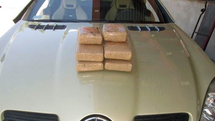 This Monday, July 20, 2015, photo released by the Customs and Border Protection Officer of Field Operations, shows cocaine valued at $134,000 found by Federal officials Sunday, July 19, hidden in Anett Pikula's Mercedes-Benz at the crossing at Lukeville, Ariz. The Phoenix woman who was said to have flirted with an officer at a border crossing station is accused of trying to smuggle 13 pounds of cocaine into the U.S. from Mexico. (Customs and Border Protection Officer of Field Operations via AP)