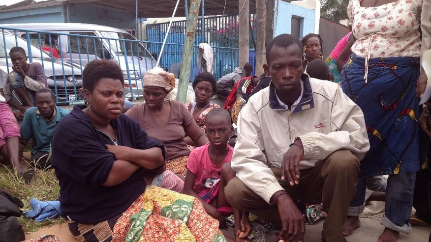 In this photo taken Friday, Aug. 14, 2015, Togo refugee Tsevi Afi, left, sits with her husband Komi Gbomagni, right,  and other refugee's outside the gates of a refugee agency in Lagos, Nigeria.  Asylum seekers who fled political violence in Togo 10 years ago are now seeking refuge in Lagos, Nigeria's commercial capital. More than 100 people, including children who have been refugees all their lives, slept by a traffic-clogged road for three nights. (AP Photo/Caelainn Hogan)