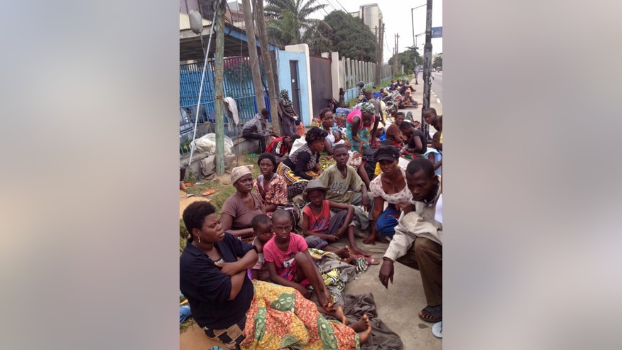 In this photo taken Friday, Aug. 14, 2015, Togo refugee Tsevi Afi, left, sit with her husband Komi Gbomagni, right,  and other refugee's outside the gates of a refugee agency in Lagos, Nigeria.  Asylum seekers who fled political violence in Togo 10 years ago are now seeking refuge in Lagos, Nigeria's commercial capital. More than 100 people, including children who have been refugees all their lives, slept by a traffic-clogged road for three nights. (AP Photo/Caelainn Hogan)