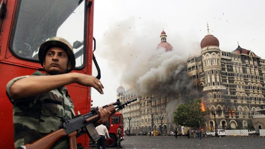 FILE- In this Nov. 29, 2008, file photo, an Indian soldier takes cover as the Taj Mahal hotel burns during gun battle between Indian military and militants inside the hotel in Mumbai, India. A Pakistani militant leader with a $10 million bounty on his head over his alleged involvement in the 2008 Mumbai terror attacks now has a new target: A Bollywood film that imagines him being assassinated. (AP Photo/David Guttenfelder, File)