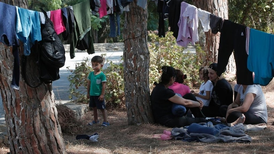 Syrian refugees pass time under the trees on the grounds of the hospital in the island of Leros, Greece, Monday, Aug. 17, 2015. This Greek island that was once a place of exile for political prisoners has become one of the country's most welcoming communities for migrants fleeing chaos and war, thanks to a dedicated grass-roots volunteer network and tourists interrupting their vacations to provide what help they can. But even on Leros, a 75-square kilometer (29 sq. mile) rocky outcrop in the Aegean Sea with a permanent population of fewer than 10,000 people, the welcome mat is fraying under the sheer numbers of migrants _ hundreds arrive in smugglers' boats most days _ making the perilous boat journey here across the Aegean Sea from Turkey. (AP Photo/Lefteris Pitarakis)