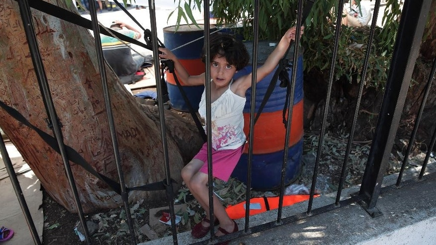 A migrant girl plays in the grounds of the headquarters of the local coast guard in the Greek island of Leros, Monday, Aug. 17, 2015. This Greek island that was once a place of exile for political prisoners has become one of the country's most welcoming communities for migrants fleeing chaos and war, thanks to a dedicated grass-roots volunteer network and tourists interrupting their vacations to provide what help they can. But even on Leros, a 75-square kilometer (29 sq. mile) rocky outcrop in the Aegean Sea with a permanent population of fewer than 10,000 people, the welcome mat is fraying under the sheer numbers of migrants _ hundreds arrive in smugglers' boats most days _ making the perilous boat journey here across the Aegean Sea from Turkey. (AP Photo/Lefteris Pitarakis)
