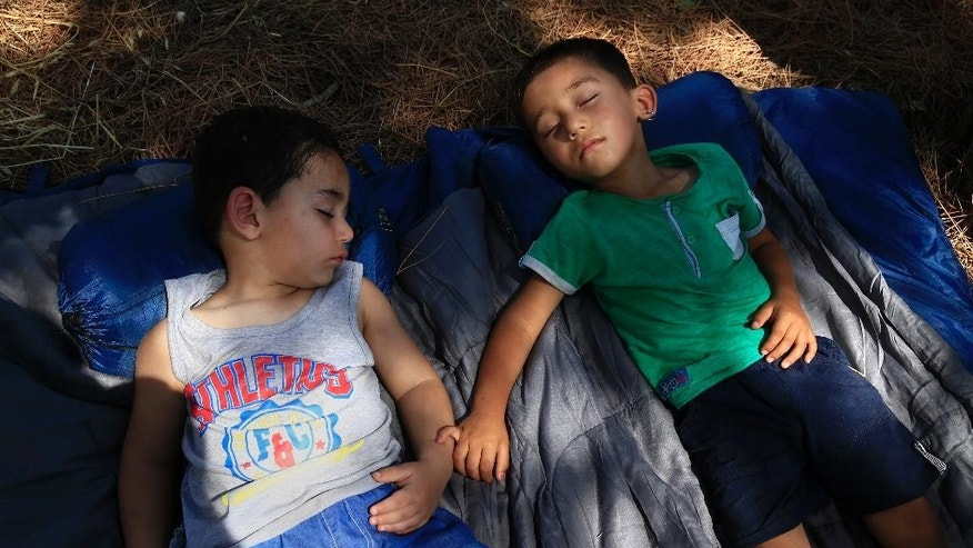 Abdul Rahman, 4, right, and his friend Miran Ali, left, both from Afghanistan sleep together under the trees on the grounds of the hospital in the Greek island of Leros, Monday, Aug. 17, 2015. This Greek island that was once a place of exile for political prisoners has become one of the country's most welcoming communities for migrants fleeing chaos and war, thanks to a dedicated grass-roots volunteer network and tourists interrupting their vacations to provide what help they can. But even on Leros, a 75-square kilometer (29 sq. mile) rocky outcrop in the Aegean Sea with a permanent population of fewer than 10,000 people, the welcome mat is fraying under the sheer numbers of migrants _ hundreds arrive in smugglers' boats most days _ making the perilous boat journey here across the Aegean Sea from Turkey. (AP Photo/Lefteris Pitarakis)
