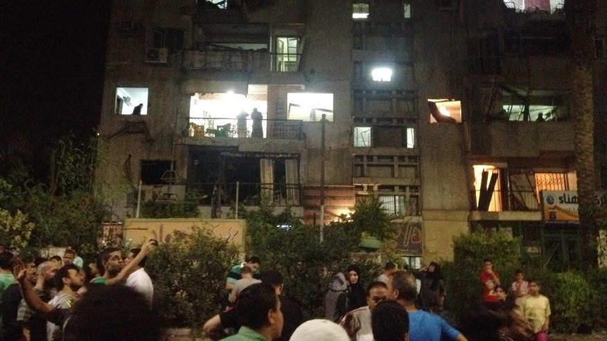 People gather by the scene where a bomb exploded early Thursday, Aug. 20, 2015, near a national security building in the Shubra neighborhood of Cairo. For blocks around the blast site in the popular residential neighborhood, glass from blown-out windows could be seen on the street. (AP Photo/Brian Rohan)