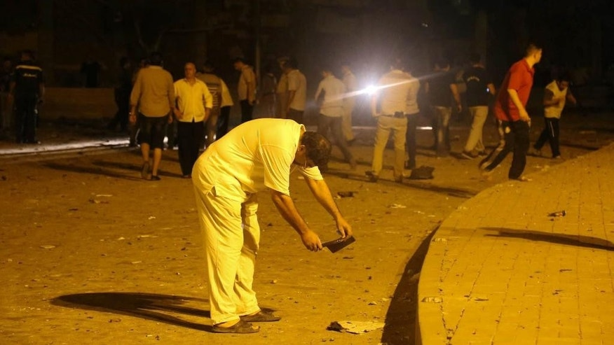 A man takes pictures after a bomb exploded early Thursday, Aug. 20, 2015, near a national security building in the Shubra neighborhood of Cairo, wounding several people, Egyptian security officials said. (AP Photo/ Mohamed Madian)