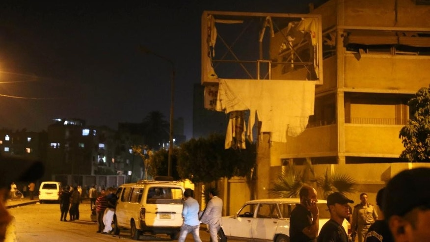 People gather after a bomb exploded early Thursday, Aug. 20, 2015, near a national security building in the Shubra neighborhood of Cairo, wounding several people, Egyptian security officials said. (AP Photo/ Mohamed Madian)