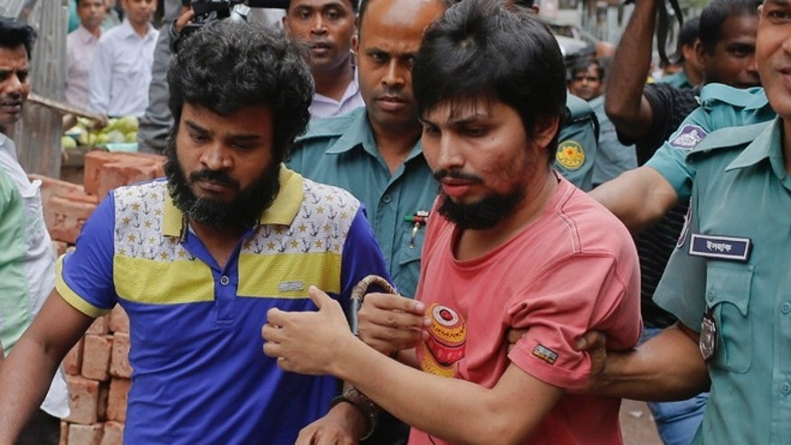 Suspected members of the banned Islamic militant outfit Ansarullah Bangla Team, Sadek Ali, second right, and Aminul Mollick, front left, are escorted by policemen along with another suspect from a court in Dhaka, Bangladesh.