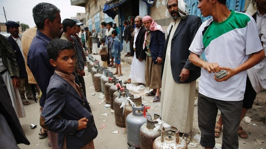 Yemeni people stand in a line to buy canisters of gas, after waiting for hours at a street in Sanaa, Yemen, Tuesday, Aug. 18, 2015. The Saudi-imposed blockade has created severe shortages of gas, petrol, and other goods, causing prices to skyrocket. (AP Photo/Hani Mohammed)