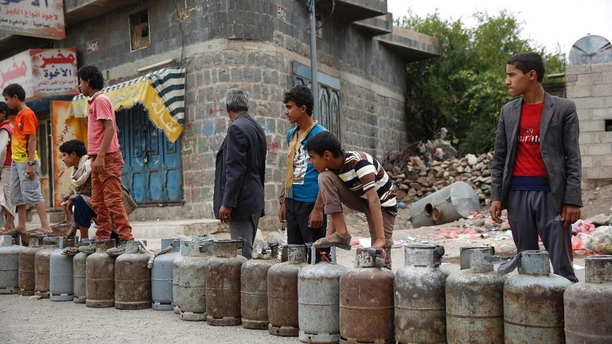 Yemeni people stand in a line to buy a canister of gas at a street in Sanaa, Yemen, Tuesday, Aug. 18, 2015. The Saudi-imposed blockade has created severe shortages of gas, petrol, and other goods, causing prices to skyrocket. (AP Photo/Hani Mohammed)