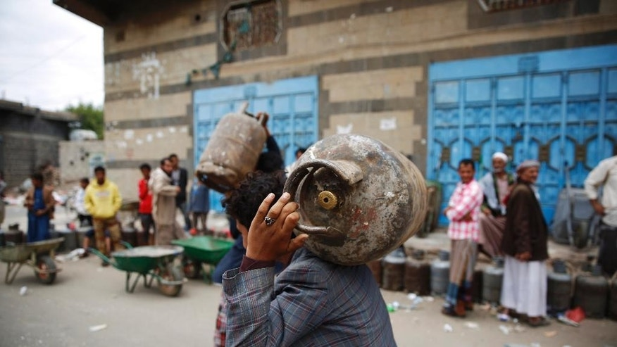 A Yemeni man carries a canister of gas he bought it after waiting for hours in Sanaa, Yemen, Tuesday, Aug. 18, 2015. The Saudi-imposed blockade has created severe shortages of gas, petrol, and other goods, causing prices to skyrocket. (AP Photo/Hani Mohammed)