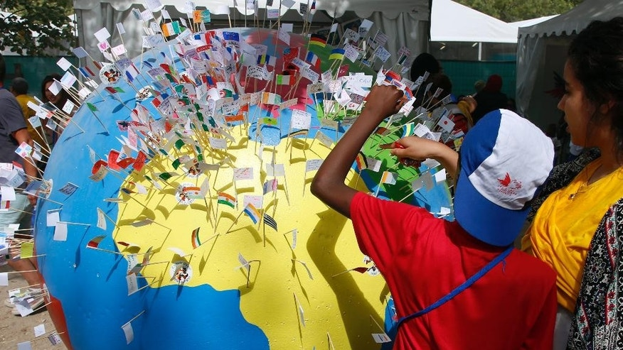 Children put little flags on a giant globe during the Vacation for Everyone day event at the Eiffel Tower in Paris, France, Wednesday Aug. 19, 2015. The French charity Secours Populaire brought children from dozens of different countries, including those living through war, poverty or natural disasters, to join kids from France for a day of summer fun, allowing even those with limited means to take a vacation at the height of the French holiday season. (AP Photo/Francois Mori)