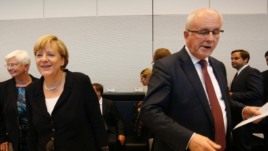 Aug. 18, 2015: German Chancellor Angela Merkel, left, smiles as parliamentary faction leader Volker Kauder opens a meeting of the Christian Democratic Party's parliamentary faction on the eve of Wednesday's vote on another bailout package for Greece, in the German Bundestag in Berlin.