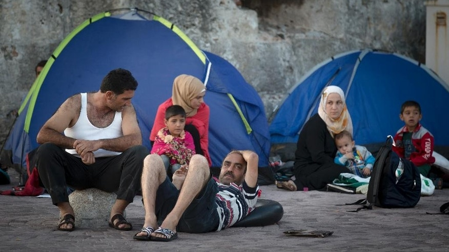 Migrants rest by their tents while waiting to be registered at the southeastern island of Kos, Greece, Wednesday, Aug. 19, 2015. More than 130,000 migrants have reached Greece so far in 2015, straining the country's resources. (AP Photo/Alexander Zemlianichenko)