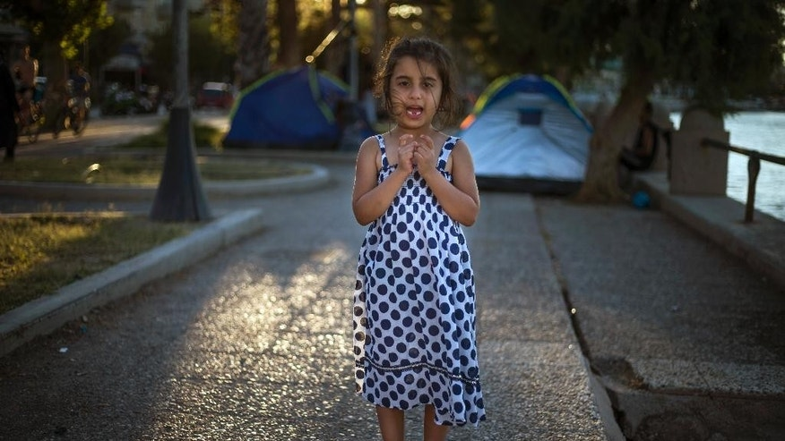 An Iraqi migrant girl rescued from a dinghy when crossing the sea from Turkey, stands at an unofficial tent camp, on the southeastern island of Kos, Greece, late Tuesday, Aug. 18, 2015. Greek authorities say they are planning to use a ferry currently docked at the island of Kos to transport up to 2,500 migrants to a northern port. (AP Photo/Alexander Zemlianichenko)