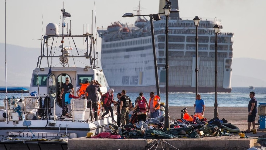 Migrants rescued from their dinghy in their attempt to cross the sea from Turkey disembark a coast guard boat at a port as the ferry Eleftherios Venizelos, background, with Syrian migrants on board leaves the southeastern island of Kos, Greece, Wednesday, Aug. 19, 2015, to travel to Thessaloniki. The ferry, which has served as a temporary migrant screening center, has about 1,700 people on board and will pick up hundreds more from other islands on the way. More than 130,000 migrants have reached Greece so far in 2015, straining the country's resources. (AP Photo/Alexander Zemlianichenko)