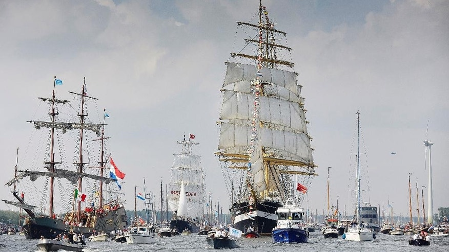 Russian tall ship the Kruzenshtern, center right, arrives in Amsterdam, Netherlands, Wednesday, Aug. 19, 2015, to participate in SAIL Amsterdam 2015, a five-yearly festival celebrating the Dutch capital's maritime history that is expected to draw some 2 million visitors. The 9th edition of  the nautical event lasts until Sunday, Aug. 23 on and around the IJ river. (AP Photo/Phil Nijhuis)