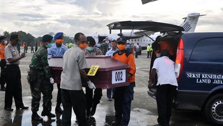 Members of the National Search and Rescue Agency carry a coffin containing a victim of the crashed Trigana Air Service flight upon arrive at Sentani airport in Jayapura, Papua province, Indonesia, Wednesday, Aug.19, 2015. Heavy fog and bad weather hampered rescuers Wednesday trying to evacuate bodies in eastern Indonesia where a passenger plane crashed into a mountain over the weekend, killing all 54 people on board, officials said.(AP Photo/Alfian)