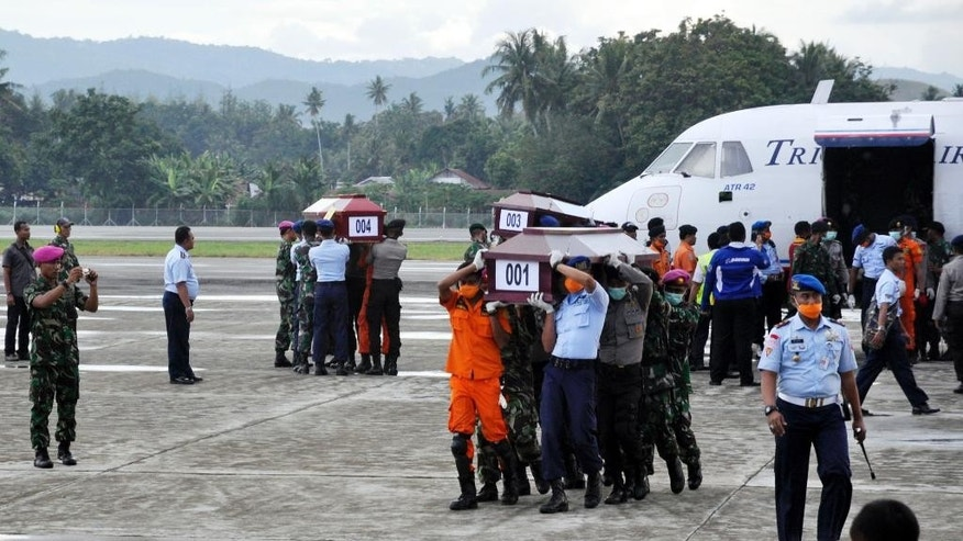 Members of the National Search and Rescue Agency carry coffins with the victims of the crashed Trigana Air Service flight upon arrive at Sentani airport in Jayapura, Papua province, Indonesia, Wednesday, Aug.19, 2015. Heavy fog and bad weather hampered rescuers Wednesday trying to evacuate bodies in eastern Indonesia where a passenger plane crashed into a mountain over the weekend, killing all 54 people on board, officials said.(AP Photo/Alfian)