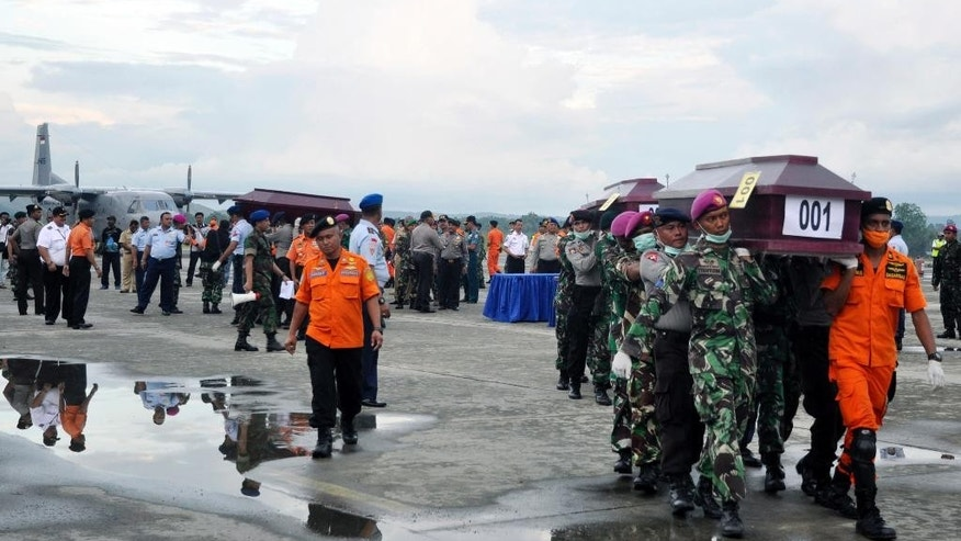 Members of the National Search and Rescue Agency carry coffins containing the victims of the crashed Trigana Air Service flight upon arrive at Sentani airport in Jayapura, Papua province, Indonesia, Wednesday, Aug.19, 2015. Heavy fog and bad weather hampered rescuers Wednesday trying to evacuate bodies in eastern Indonesia where a passenger plane crashed into a mountain over the weekend, killing all 54 people on board, officials said.(AP Photo/Alfian)