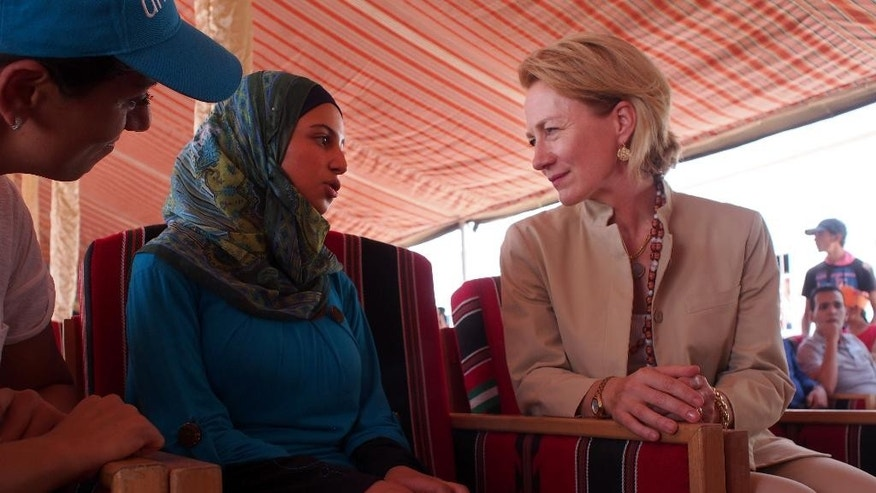 U.S. Ambassador Alice Wells talks with Syrian girls' education activist and refugee Mezon al-Meliha in Jordan's Azraq refugee camp on Wednesday, August, 19, 2015. Wells was among a group of officials inaugurating both a new well for the refugee camp and the school for continuing education for Syrians. (AP Photo/Sam McNeil)