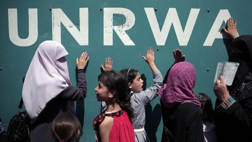 "Palestinians demonstrate against a U.N. Relief and Works Agency (UNRWA) funding gap that could keep about 500,000 Palestinian students out of school this fall, outside the UNRWA Gaza Headquarters in Gaza City, Sunday, Aug. 16, 2015. The deputy chief of the UNRWA, which operates 700 schools, Sandra Mitchell, said Monday that ""if funding does not arrive"" this month, the agency could delay the start of the school year. (AP Photo/Khalil Hamra)"