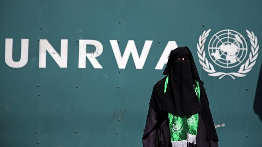 "A Palestinian woman wears a green Hamas scarf attends a demonstration against a U.N. Relief and Works Agency (UNRWA) funding gap that could keep about 500,000 Palestinian students out of school this fall, outside the UNRWA Gaza Headquarters in Gaza City, Sunday, Aug. 16, 2015. The deputy chief of the UNRWA, which operates 700 schools, Sandra Mitchell, said that ""if funding does not arrive"" this month, the agency could delay the start of the school year. (AP Photo/Khalil Hamra)"
