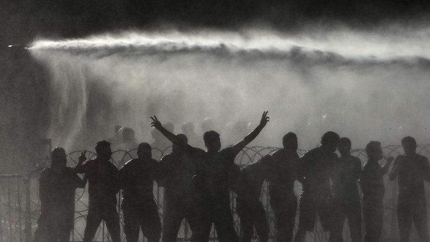 "Lebanese activists are sprayed by riot police using water cannons, during a protest against the ongoing trash crisis, in front of the government house, in downtown Beirut, Lebanon, Wednesday, Aug. 19, 2015. Lebanon's health minister says the country is on the brink of a ""major health disaster"" unless an immediate solution is found for its mounting trash problem. Garbage has been collecting on the streets in Lebanon for the past month amid government paralysis and inability to agree on a solution after Beirut's main landfill was closed down. (AP Photo/Hussein Malla)"