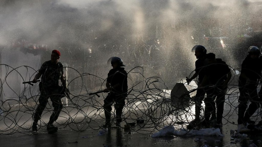 "Lebanese riot police reassemble the barbed wire, which was removed by angry activists during a protest against the ongoing trash crisis, in front the government house, in downtown Beirut, Lebanon, Wednesday, Aug. 19, 2015. Lebanon's health minister says the country is on the brink of a ""major health disaster"" unless an immediate solution is found for its mounting trash problem. Garbage has been collecting on the streets in Lebanon for the past month amid government paralysis and inability to agree on a solution after Beirut's main landfill was closed down. (AP Photo/Hussein Malla)"