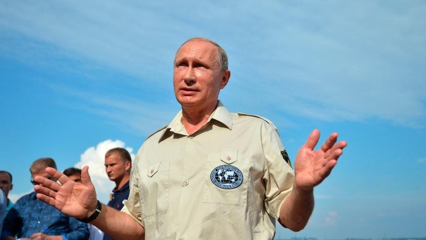 Russian President Vladimir Putin speaks to the media in Sevastopol, Crimea, after plunging below the waves aboard a submersible craft into the Black Sea, in Sevastopol, Crimea, Tuesday, Aug. 18, 2015.   Putin traveled aboard the small submersible craft down to the seabed of the Black Sea to view an ancient Byzantine trading ship recently discovered off the coast of Crimea. (Alexei Druzhinin/RIA-Novosti, Kremlin Pool Photo via AP)