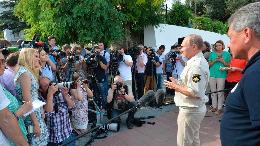 Russian President Vladimir Putin speaks to local residents and the media after plunging aboard a submersible craft into the Black Sea, in Sevastopol, Crimea, Tuesday, Aug. 18, 2015.   Putin traveled aboard the small submersible craft down to the seabed of the Black Sea to view an ancient Byzantine trading ship recently discovered off the coast of Crimea.(Alexei Druzhinin/RIA-Novosti, Kremlin Pool Photo via AP)