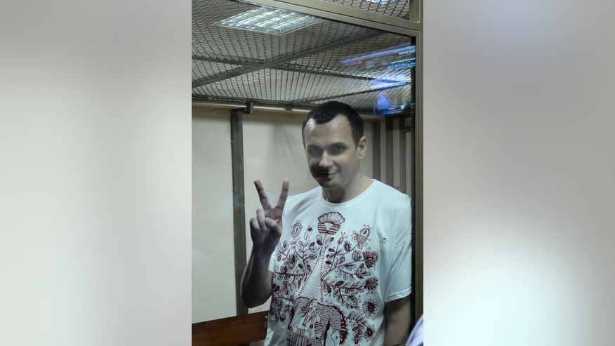 FILE - In this Tuesday, July  21, 2015 file photo Oleg Sentsov gestures as he stands behind glass in a cage at a court room in Rostov-on-Don, Russia. Russian prosecutors are asking a court to send a Ukrainian filmmaker to prison for 23 years on charges of conspiracy to commit terrorist attacks on Wednesday, Aug. 19, 2015. (AP Photo, File)