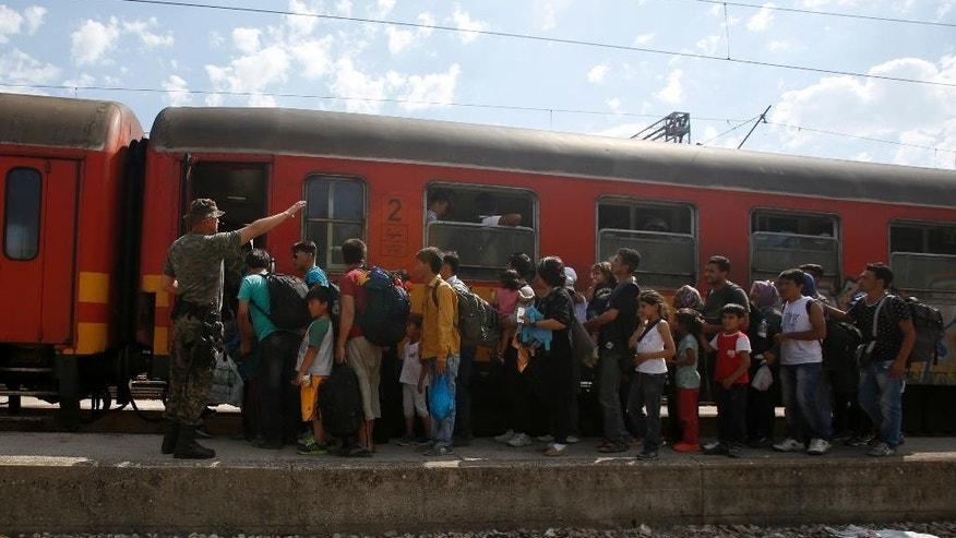 Migrants wait to board a train headed for Serbia, at the railway station in the southern Macedonian town of Gevgelija, Wednesday, Aug. 19, 2015. Record numbers of migrants from countries like Syria, Iraq and Afghanistan uses the so-called Balkan route that passes trough Macedonia. (AP Photo/Darko Vojinovic)