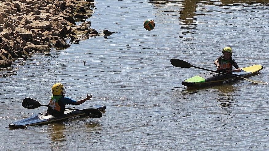 Children from a kayak club play water ball in hot summer weather on the Vistula River  in Warsaw, Poland, Tuesday, Aug. 18, 2015. (AP Photo/Czarek Sokolowski)