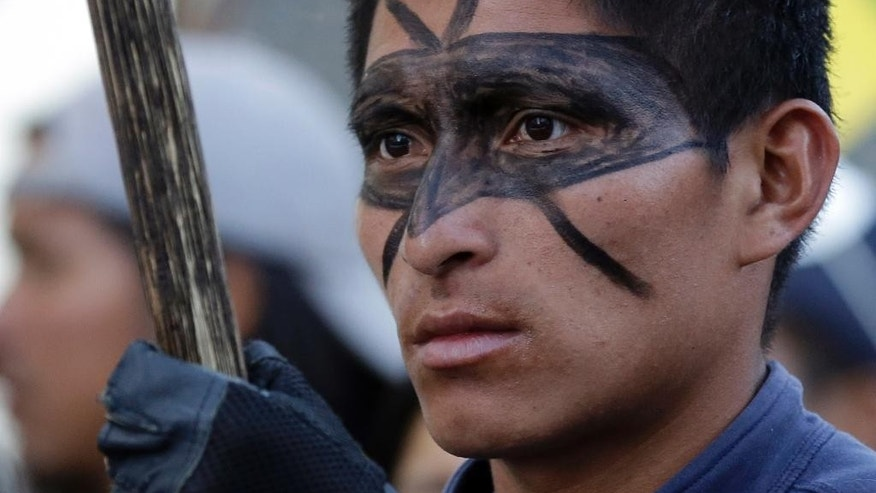 An Indian from the Amazon region of Ecuador takes part in a protest march in Quito, Ecuador, Wednesday, Aug. 19, 2015. The march was called by labor unions and indigenous organizations to protests against policies of President Rafeal Correa. (AP Photo/Dolores Ochoa)