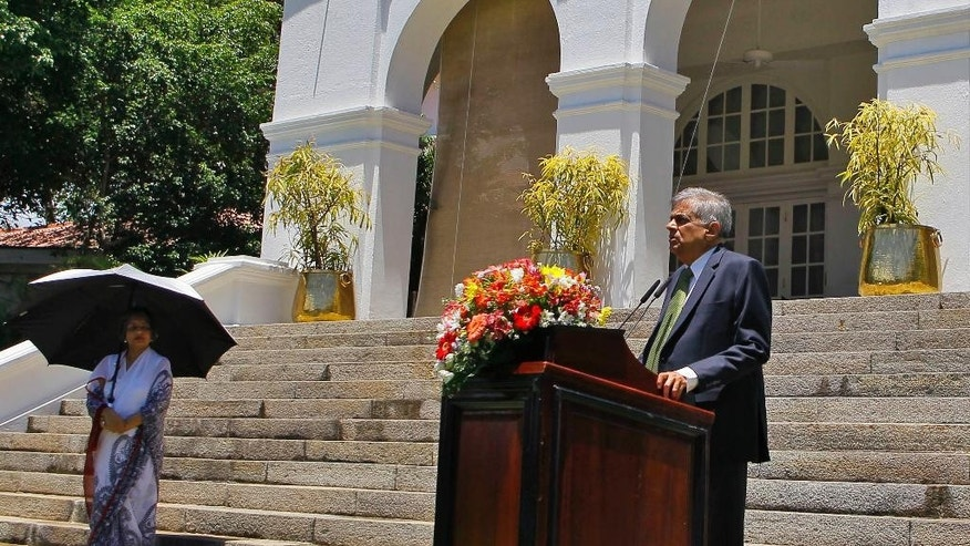 Sri Lanka's prime minister Ranil Wickremesinghe speaks as his wife Maithree watches during a media interaction at his official residence in Colombo, Sri Lanka, Wednesday, Aug. 19, 2015. Wickremesinghe defeated the country's former strongman Mahinda Rajapaksa in parliamentary elections, according to results released Tuesday, Aug. 18, 2015, blocking a key step of his bid to return to power eight months after he lost the presidency. (AP Photo/Eranga Jayawardena)