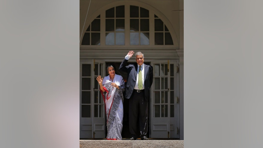 ALTERNATE CROP TO DEL106 - Sri Lanka's prime minister Ranil Wickremesinghe and his wife Maithree wave to media at their official residence in Colombo, Sri Lanka, Wednesday, Aug. 19, 2015. Wickremesinghe defeated the country's former strongman Mahinda Rajapaksa in parliamentary elections, according to results released Tuesday, Aug. 18, 2015, blocking a key step of his bid to return to power eight months after he lost the presidency. (AP Photo/Eranga Jayawardena)
