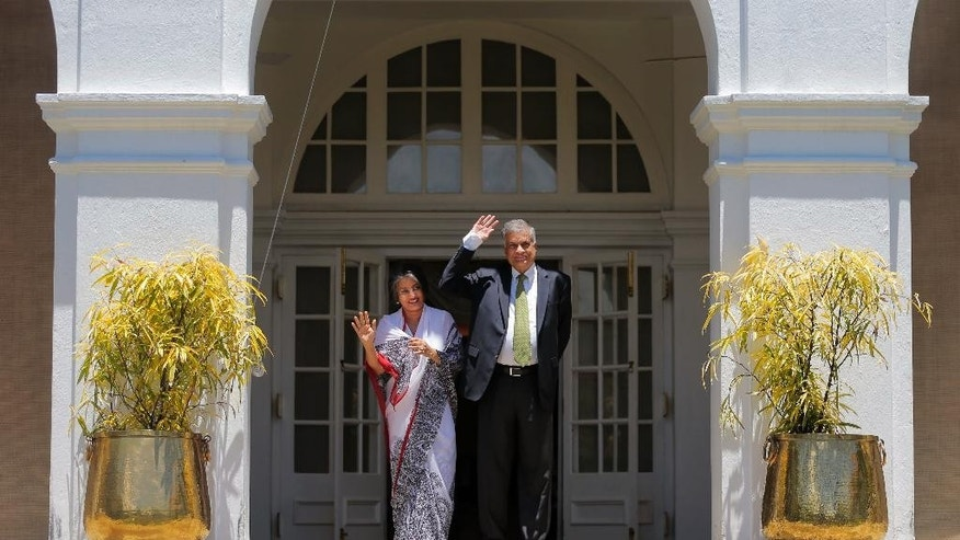 Sri Lanka's prime minister Ranil Wickremesinghe and his wife Maithree wave to media at their official residence in Colombo, Sri Lanka, Wednesday, Aug. 19, 2015. Wickremesinghe defeated the country's former strongman Mahinda Rajapaksa in parliamentary elections, according to results released Tuesday, Aug. 18, 2015, blocking a key step of his bid to return to power eight months after he lost the presidency. (AP Photo/Eranga Jayawardena)