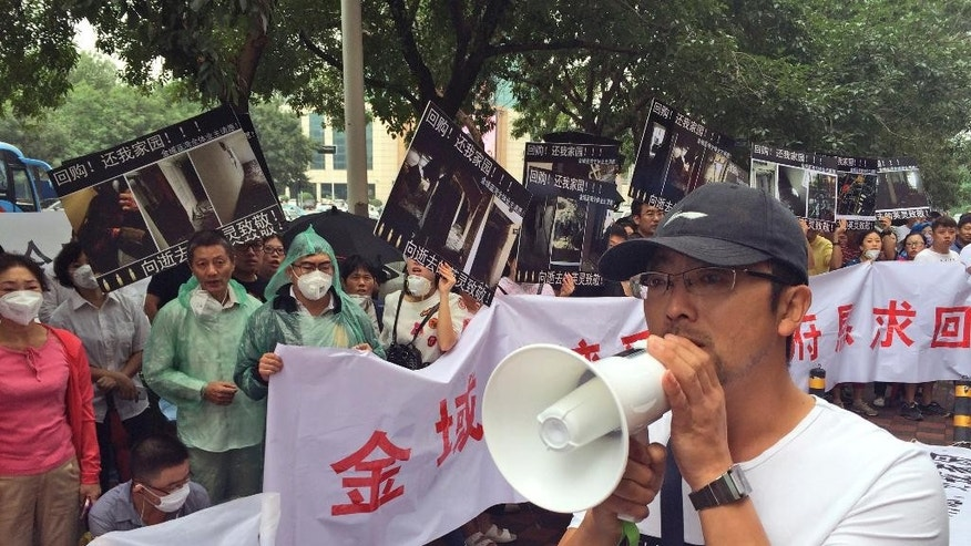 Residents demanding compensation for damages to their homes after an explosion at the Tianjin port protest outside a hotel where media press conferences are held in northeastern China's Tianjin municipality on Wednesday, Aug. 19, 2015. The blasts originated at a warehouse for hazardous material, where 700 tons of sodium cyanide — a toxic chemical that can form combustible substances on contact with water — was being stored in amounts that violated safety rules. (AP Photo/Paul Traynor)