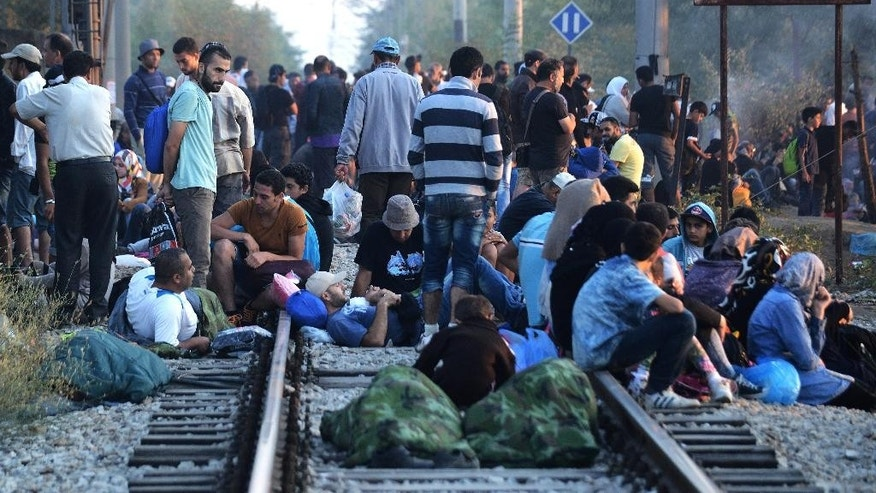 FOR WEDNESDAY AUG. 19, 2015 STORY MIGRANTS LOST IN TRANSIT BY KOSTAS KADOURIS - In this picture made on Wednesday, Aug. 12, 2015, Syrian refugee wait at a railroad track of  Idomeni,  northern Greece. Bureaucratic mistakes and oversights by Greek officials overwhelmed by an unprecedented refugee influx are making life harder for thousands transiting through Greece as they flee war in Syria, but are caught with Greek transit papers that are faulty because of careless mistakes by overwhelmed officials. (AP Photo/Giannis Papanikos)