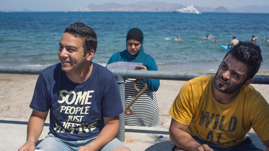 FOR WEDNESDAY AUG. 19, 2015 STORY MIGRANTS LOST IN TRANSIT BY KOSTAS KADOURIS - In this picture made on Thursday, Aug. 13, 2015, Syrian refugee Jaber Ahmed Samer, left, and Subhl Jasim Swadi, hold their travel papers as they sit on the beachfront at Kos island, Greece.  Bureaucratic mistakes and oversights by Greek officials overwhelmed by an unprecedented refugee influx are making life harder for thousands transiting through Greece as they flee war in Syria, but are caught with Greek transit papers that are faulty because of careless mistakes by overwhelmed officials.(AP Photo/Alexander Zemlianichenko)