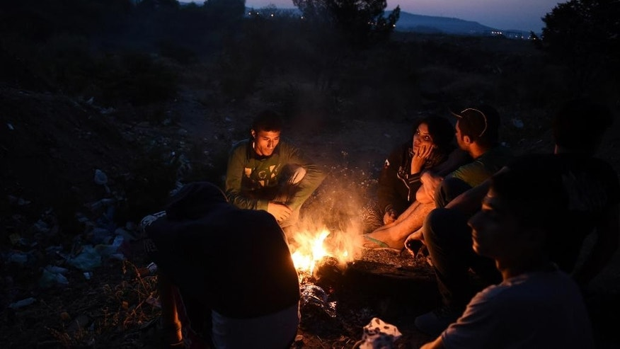 FOR WEDNESDAY AUG. 19, 2015 STORY MIGRANTS LOST IN TRANSIT BY KOSTAS KADOURIS -In this picture made on Wednesday, Aug. 12, 2015, Syrian refugees sit near a fire to keep warm near the border train station of Idomeni,  northern Greece,  as they wait to be allowed by the Macedonian police to cross the border from Greece to Macedonia.  Bureaucratic mistakes and oversights by Greek officials overwhelmed by an unprecedented refugee influx are making life harder for thousands transiting through Greece as they flee war in Syria, but are caught with Greek transit papers that are faulty because of careless mistakes by overwhelmed officials.(AP Photo/Giannis Papanikos)