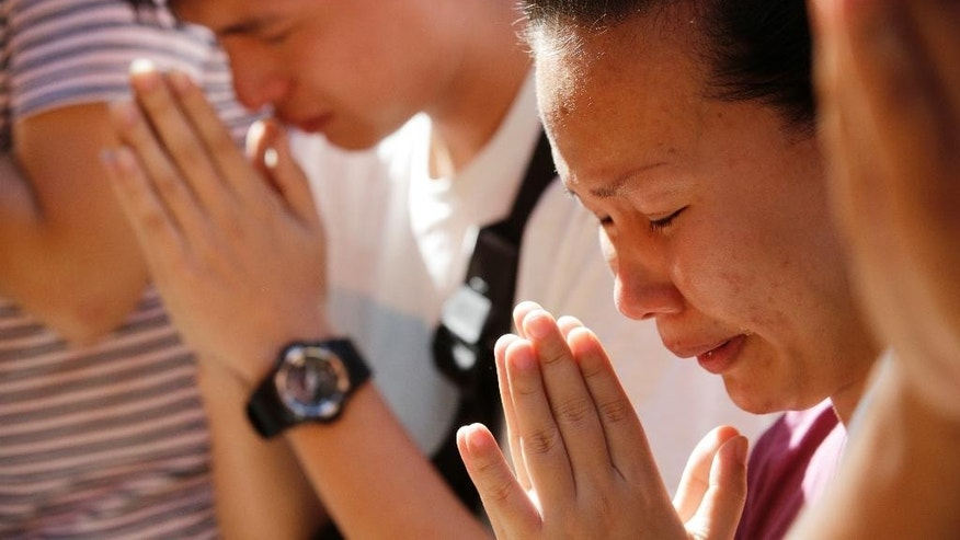 Family members of a bombing victim pray at the Erawan Shrine at Rajprasong intersection in Bangkok, Thailand, Wednesday, Aug. 19, 2015. A central Bangkok shrine reopened Wednesday to the public after Monday's bomb blast as authorities searched for a man seen in a grainy security video who they say was the prime suspect in an attack authorities called the worst in the country's history. (AP Photo/Sakchai Lalit)