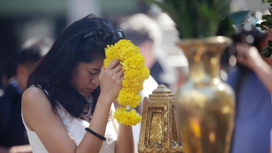 A woman prays at the Erawan Shrine at Rajprasong intersection in Bangkok, Thailand, Wednesday, Aug. 19, 2015. The central Bangkok shrine reopened Wednesday after Monday's bomb blast to the public as authorities searched for a man seen in a grainy security video who they say was the prime suspect in an attack authorities called the worst in the country's history. (AP Photo/Sakchai Lalit)