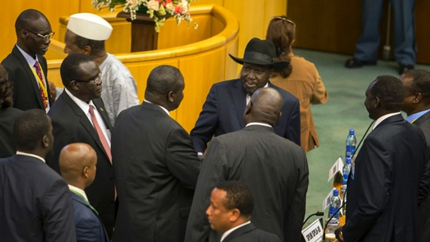 Aug. 17, 2015: South Sudan's rebel leader Riek Machar, center-left with back to camera, shakes hands with South Sudan's President Salva Kiir, center-right wearing a black hat, after lengthy peace negotiations in Addis Ababa, Ethiopia. Kiir refused to sign a peace agreement Monday with rebel forces, saying he needs 15 days before he will sign, although Machar had signed the accord before Kiir refused. (AP Photo/Mulugeta Ayene)