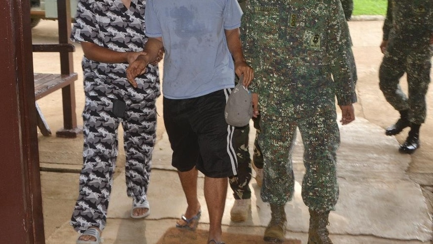 Escaped hostage Philippine coast guard Seaman First Class (SN1) Rod Pagaling, center, is escorted inside a military camp in Jolo, Sulu province, southern Philippines Thursday, Aug. 20, 2015. Two Philippine coast guard personnel, Pagaling and Gringo Villaruz who were threatened with beheading escaped from their Abu Sayyaf extremist captors when hundreds of troops stormed the militants' jungle base in the country's south, military officials said Thursday. (AP Photo/Nickee Butlangan)