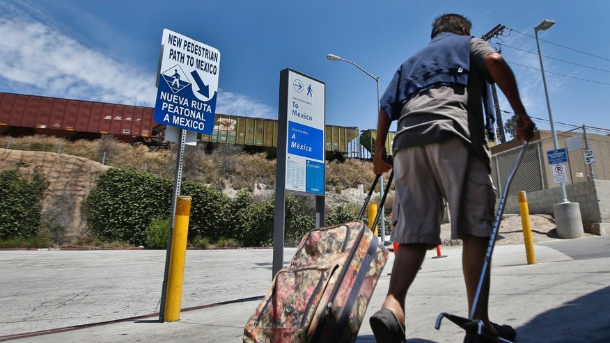 In this Aug. 18, 2015 photo, a man pulling his luggage follows the signs to the Mexico border crossing in San Ysidro, Calif. Starting late Wednesday, Aug. 19, pedestrians going to Tijuana from San Diego at the San Ysidro crossing must choose between a line for Mexicans who get waved through, and a line for foreigners. Foreigners must show a passport, fill out a form and - if staying more than a week - pay for a six-month permit. (AP Photo/Lenny Ignelzi)